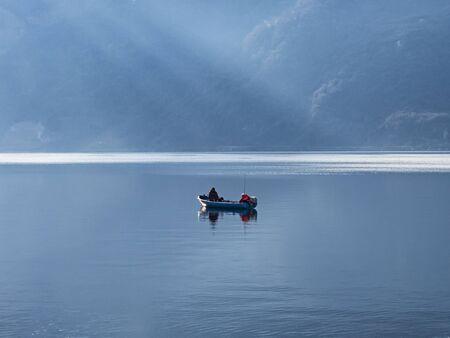 Single fisherman's boat on Lake Como