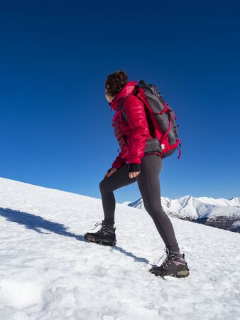 Woman hiker on a glacier with crampons on boots