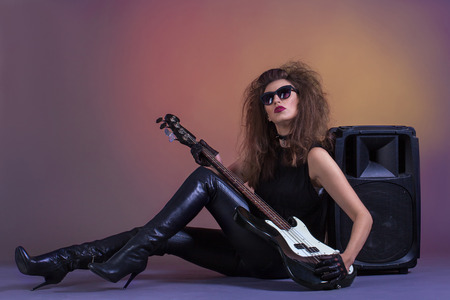 Young girl in leather pants with a bass guitar and speakers.