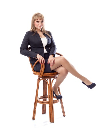 personable: Young beautiful business woman in a business suit, sitting on a bar stool. White isolated background. Stock Photo