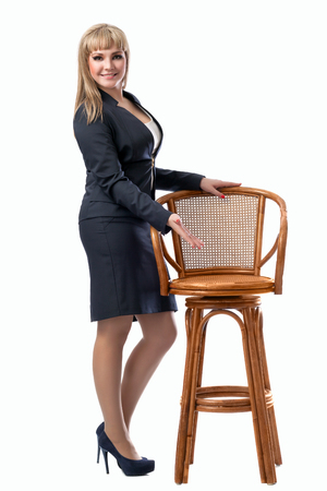 personable: Young beautiful business woman inviting to sit on a chair. White isolated background