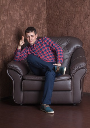 cool guy: Young successful guy sitting on a leather armchair. Cool Stock Photo