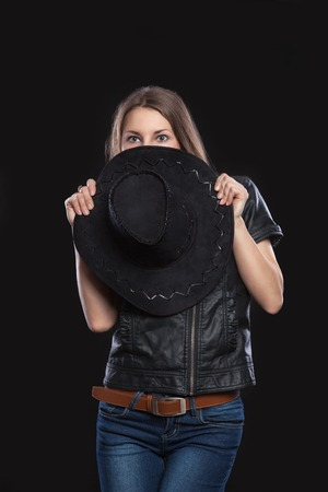 black cowgirl: A young brunette woman in a wild west style covered and hidden behind a black cowboy hat.