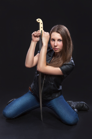 militant: Beautiful, brown-haired woman, a militant in the leather jacket is sitting on her knees and leans on her sword. Black background.