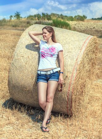 Young beautiful girl in short shorts standing in a field based on a round bale of hay and looks into the distance. Summer hot sunny day. The season of harvest.