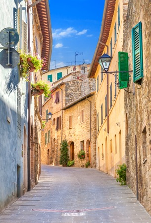 Montepulciano, Italy. Old narrow street lined with stone blocks in the center of town with colorful facades. Tourists walking along the street.