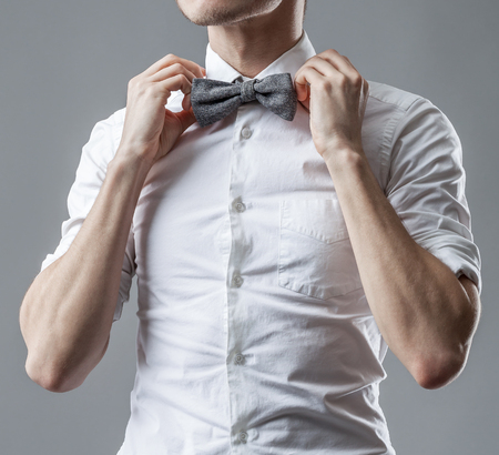 animal body part: Stylish man in a white classic shirt correcting bow tie. The official style of clothes.