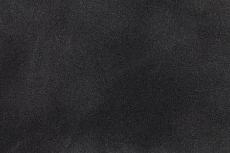 黒のスエード生地のクローズ アップ。ベルベットのテクスチャ背景