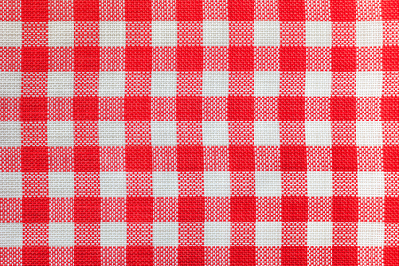 Checkered tablecloth for the table in red and white cells. Background texture of fabric napkin.