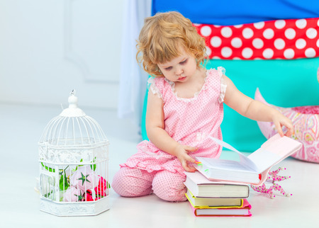 Little cute curly girl in pink pajamas watching the book sitting on the floor in the childrens bedroom.