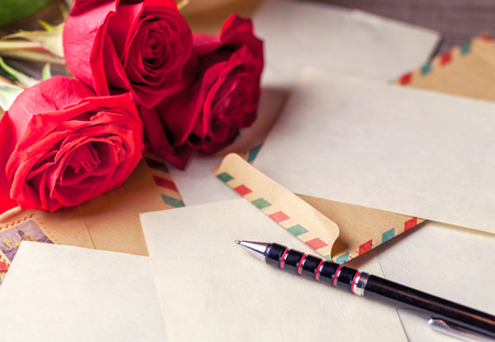 Vintage envelopes, bouquet of red roses and sheets of paper scattered on the wooden table for writing romantic letters. Stock Photo