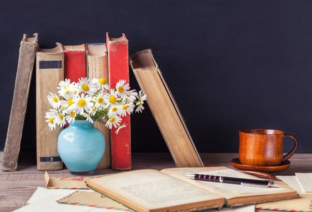 The open old book lying on the wooden table among vintage envelopes, vase with daisies and a cup with a hot drink. Rustic still life.