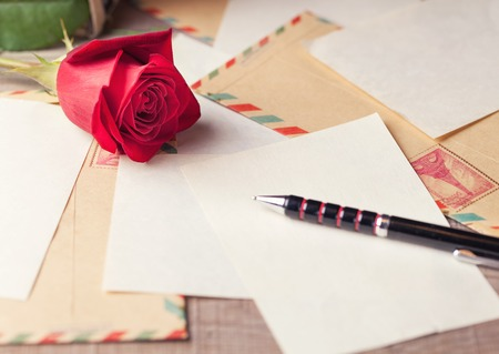 Vintage envelopes, red roses and sheets of paper scattered on the wooden table for writing romantic letters.