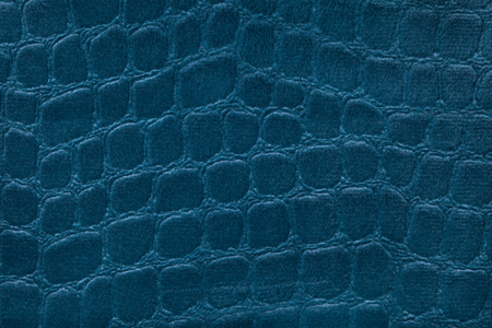 Blue background from a soft upholstery textile material, closeup. Fabric with pattern imitating crocodile skin.. Textured backdrop.