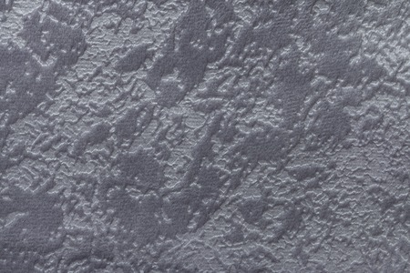Gray background from a soft upholstery textile material, closeup. Fabric with natural texture. Cloth backdrop.