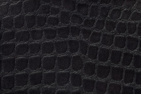 Black background from a soft upholstery textile material, closeup. Fabric with pattern imitating crocodile skin.. Textured backdrop. Stock Photo