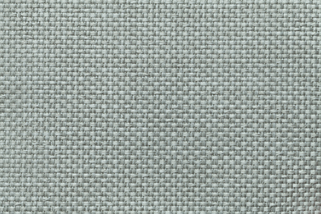 Light green background with braided checkered pattern, closeup. Texture of the weaving fabric, macro.