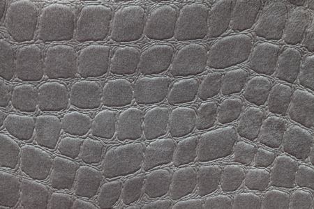 Dark gray background from a soft upholstery textile material, closeup. Silver fabric with pattern imitating crocodile skin.. Textured backdrop.