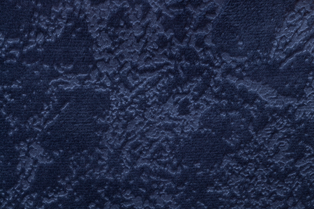 Navy blue background from a soft upholstery textile material, closeup. Denim spotted fabric with natural texture. Cloth backdrop. Stock Photo