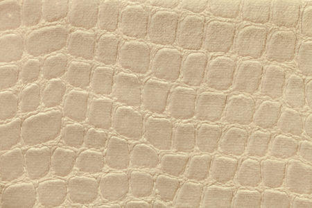 Light beige background from a soft upholstery textile material, closeup. Yellow fabric with pattern imitating crocodile skin.. Textured backdrop.