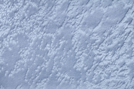 Light blue background from a soft upholstery textile material, closeup. Sky spotted fabric with natural texture. Cloth backdrop.