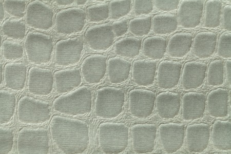 Light green background from a soft upholstery textile material, closeup. Fabric with pattern imitating crocodile skin.. Textured backdrop.