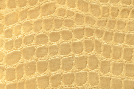 Light yellow background from a soft upholstery textile material, closeup. Golden fabric with pattern imitating crocodile skin.. Textured backdrop. Stock Photo