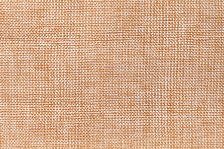 Light orange and white background of dense woven bagging fabric, closeup. Structure of the brown cloth with natural texture. Cloth backdrop.