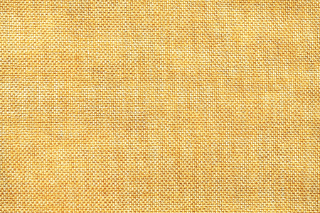 Light yellow and white background of dense woven bagging fabric, closeup. Structure of the golden cloth with natural texture. Cloth backdrop. Stock Photo