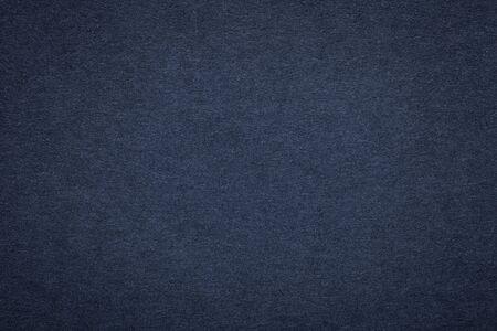Texture of old navy blue paper background, closeup. Structure of dense dark denim kraft cardboard. Stock Photo