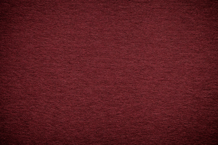 Texture of old dark red paper background, closeup. Structure of dense maroon cardboard.
