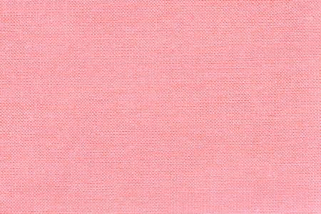 Fondo rosa claro de un material textil con patrón de mimbre, portarretrato. Estructura de la tela rosa con textura natural. Fondo de tela. Foto de archivo