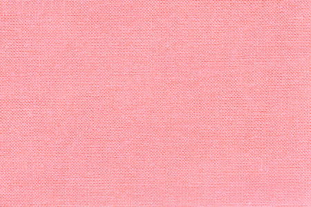 Light pink background from a textile material with wicker pattern, closeup. Structure of the rose fabric with natural texture. Cloth backdrop.