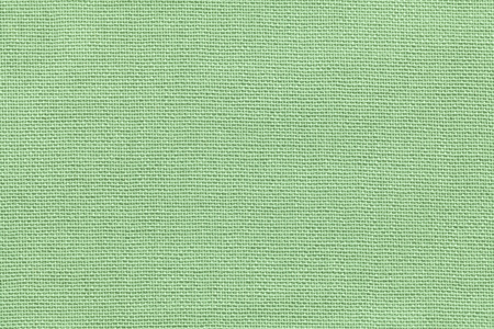 Light green background from a textile material with wicker pattern, closeup. Structure of the olive fabric with natural texture. Cloth backdrop.