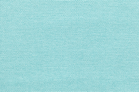 Light blue background from a textile material with wicker pattern, closeup. Structure of the pastel turquoise fabric with natural texture. Cloth backdrop. Stock Photo