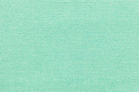 Light green background from a textile material with wicker pattern, closeup. Structure of the pastel turquoise fabric with natural texture. Cloth backdrop. Stock Photo
