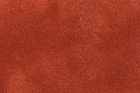 Background of dark orange suede fabric closeup. Velvet matt texture of ginger nubuck textile. Stock Photo