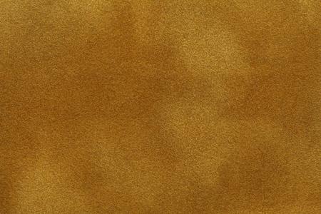 Background of golden purple suede fabric closeup. Velvet matt texture of orange nubuck textile. Stock Photo