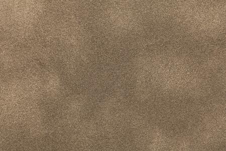 Achtergrond van de lichte close-up van de bronssuèdestof. Fluwelen matte textuur van zandnubuck textiel.