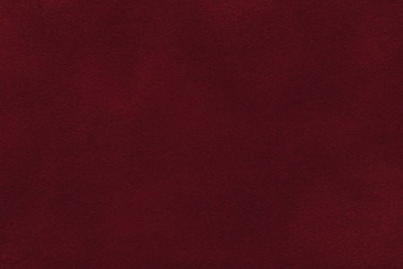 Background of dark red suede fabric closeup. Velvet matt texture of wine nubuck textile.