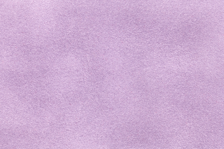Background of light violet suede fabric closeup. Velvet matt texture of lilac nubuck textile. Stock Photo