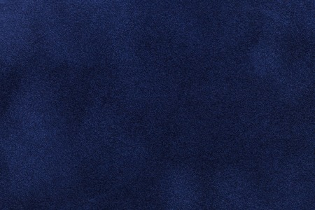Background of dark blue suede fabric closeup. Velvet matt texture of navy blue nubuck textile. 写真素材