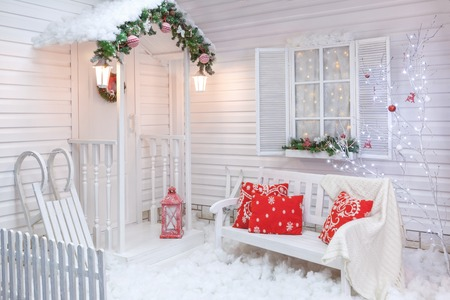 Winter exterior of a country house with Christmas decorations in the American style. Snow-covered courtyard with a porch, tree, white bench and wooden vintage sleds.