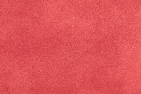 Korallenmatter Hintergrund aus Wildleder, Nahaufnahme. Samtstruktur aus nahtlosem rotem Leder. Filzmaterial Makro.