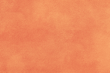 Orange matte background of suede fabric, closeup. Velvet texture of seamless coral leather. Felt materisl macro.