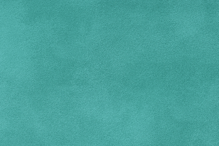 turquoise matte background of suede fabric, closeup. Velvet texture of seamless cyan leather. Felt materisl macro.