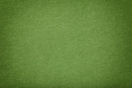 Light green matte background of suede fabric, closeup. Velvet texture of seamless olive leather with vignette. Felt materisl macro.