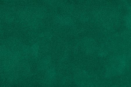 Dark green matte background of suede fabric, closeup. Velvet texture of seamless deep emerald leather. Felt materisl macro. Stock Photo
