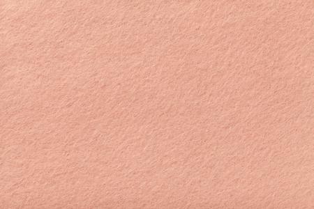 Light pink matte background of suede fabric, closeup. Velvet texture of seamless coral woolen felt. Stock Photo
