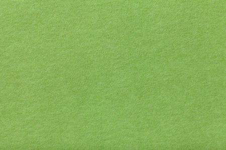 Light green matte background of suede fabric, closeup. Velvet texture of seamless olive woolen felt.